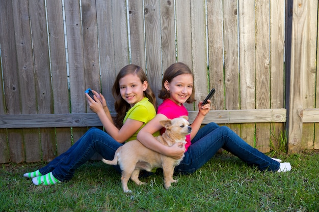 Zwillingsschwestermädchen, die smartphone und chihuahuahund spielen