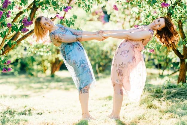 Zwillingsschwestern haben spaß an der natur. schöne zwillinge in kleidern tanzen. schöne fröhliche junge mädchen, die kindheit im sommer im freien genießen.