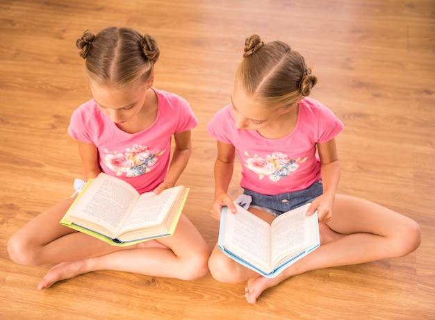 Zwillingsschwestern lesen bücher, die auf dem boden sitzen.