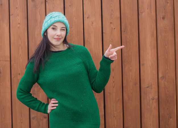 Zwinkernde europäische frau im grünen pullover und im grünen hut auf holzwand