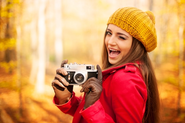 Zwinkernde frau, die foto durch retro-kamera nimmt