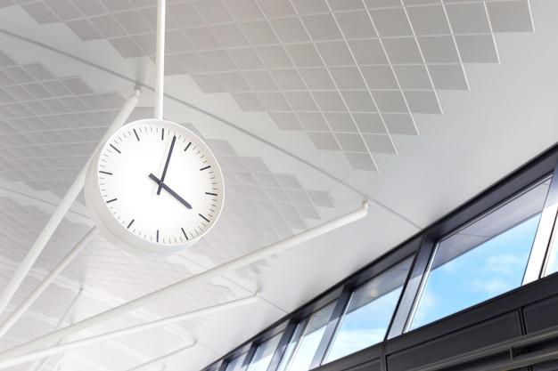 Zwischen abflug- und ankunftshalle, terminal des internationalen flughafens, hängt eine weiße uhr auf dem boden