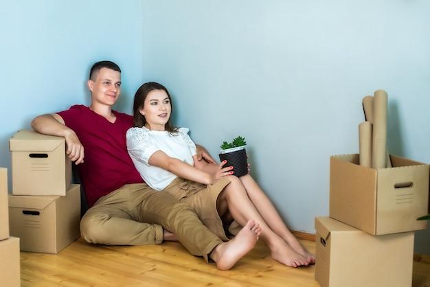 Zwischen den kisten sitzt ein junges paar auf dem boden. mann und frau sind in ein neues zuhause umgezogen und glücklich. reparatur, hypothek, einweihung. mädchen halten eine blume in ihren händen.