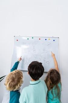 Zwischen seinen mitschülern. dunkelhaariger junge, der zwischen seinen klassenkameraden in der nähe des whiteboards steht und mülltrennung studiert