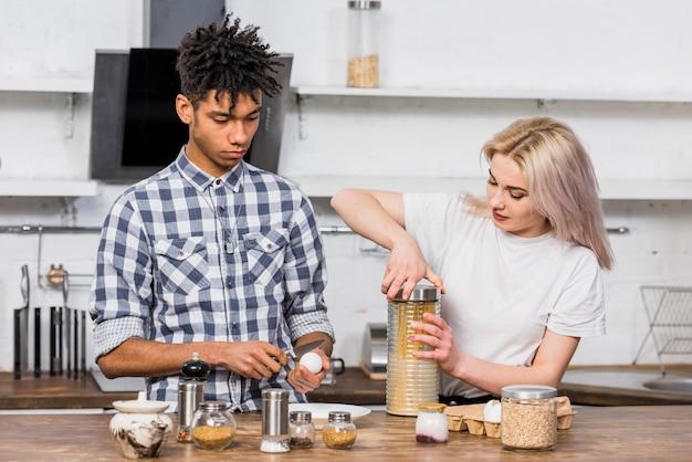 Zwischen verschiedenen rassen junge paare, welche die spaghettis in der küche zubereiten