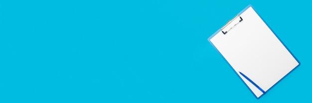Zwischenablage mit einem leeren blatt und einem stift auf einem hellblauen