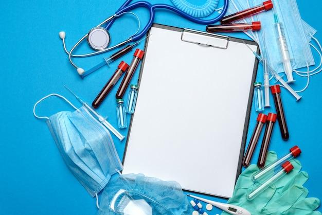 Zwischenablage mit leerem blatt papier mit medizinischen werkzeugen auf blau