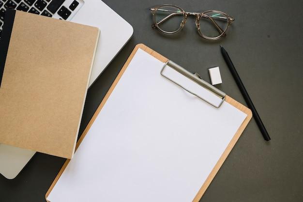 Zwischenablage und brille in der nähe von laptop