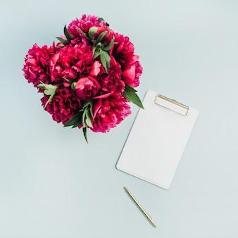 Zwischenablage und rosa pfingstrosenblumenstrauß auf pastellblauer oberfläche