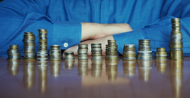 Zwölf stapel münzen auf einem schreibtisch mit mann im blauen hemd im hintergrund. saisonales verkaufskonzept jährliche analyse