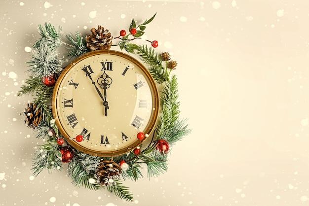 Zwölf uhr, wie silvester. gold vintage uhr in einem weihnachtsdekor auf weißem hintergrund. platz kopieren