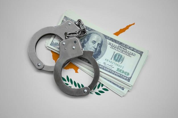 Zypern-flagge mit handschellen und einem bündel dollar. währungskorruption im land. finanzielle verbrechen