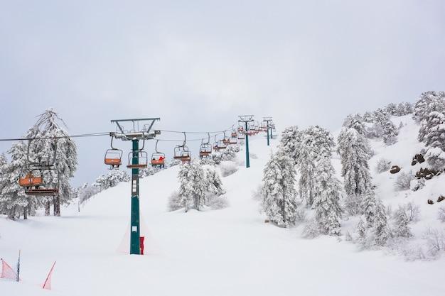 Zypern. skilifte und seilbahnen fahren den berg hinauf und bringen snowboarder auf die skipisten.
