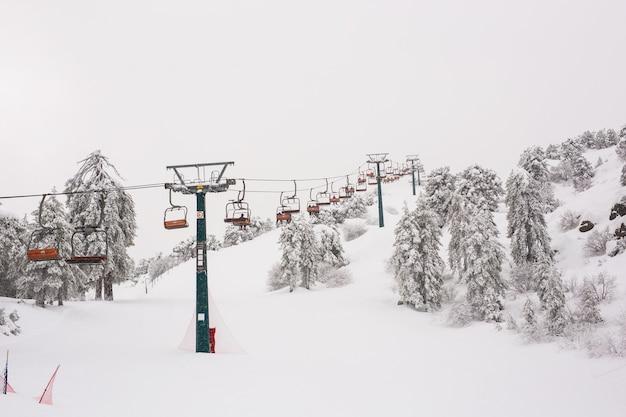 Zypern, troodos berge. skilifte und seilbahnen fahren den berg hinauf und bringen snowboarder nach