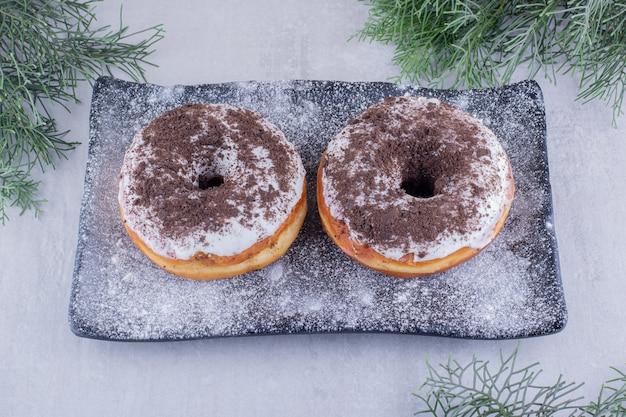 Zypressenblätter um eine mit mehl bedeckte platte mit zwei donuts oben auf weißem hintergrund.