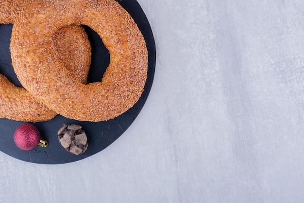 Zypressenkegel, weihnachtsdekor und mit sesam beschichtete bagels auf einer schwarzen tafel auf weißem hintergrund.