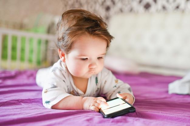 電話への子供の依存症。電話から子供への放射線。スマートフォンを手に持った0〜1歳の小さな男の子は、熱意を持って画面を見ています。子ガジェット中毒
