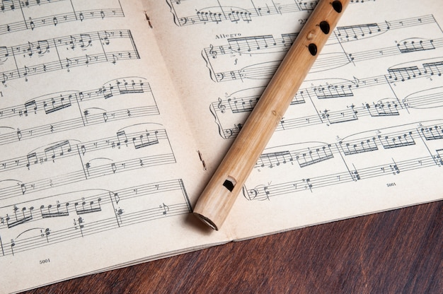 07-06-2020 баку.азербайджан. винтажная бамбуковая флейта поверх старинных музыкальных нот