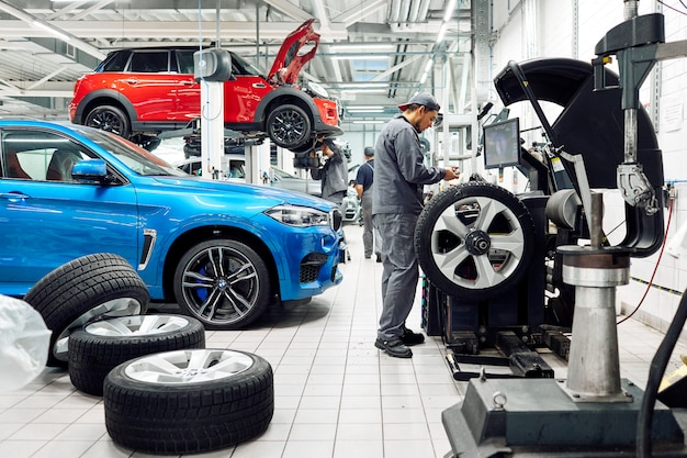 モスクワ、ロシア、09.05.2019、自動車修理店で車を修理する男性、多くの車輪、bmw、タイヤフィッティング