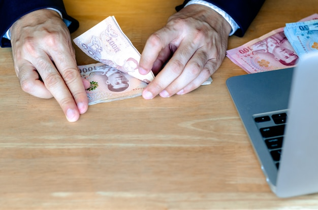 男の手が新しいタイのお金1,000バーツ紙幣を数えます。