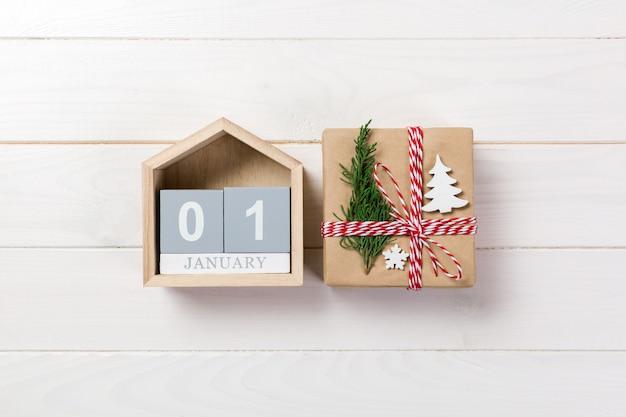 クリスマスカレンダー1月1日。クリスマスプレゼント、木製の白い背景のモミの枝。 copyspace、トップビュー