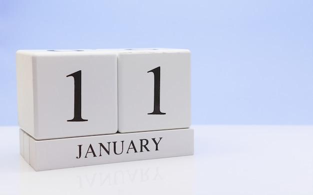 1月11日月の11日目、反射と白いテーブルの上の毎日のカレンダー