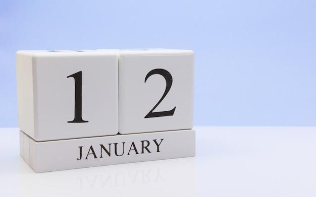 1月12日月の12日目、反射と白いテーブルに毎日のカレンダー