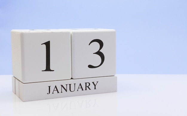 1月13日月の13日目、反射と白いテーブルに毎日のカレンダー