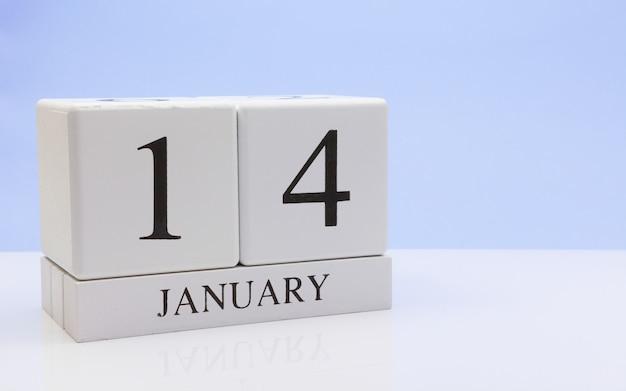 1月14日月の14日、反射と白いテーブルに毎日のカレンダー
