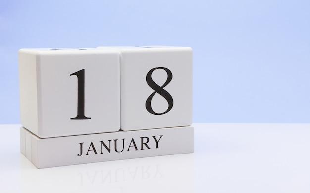 1月18日月18日、反射と白いテーブルに毎日のカレンダー