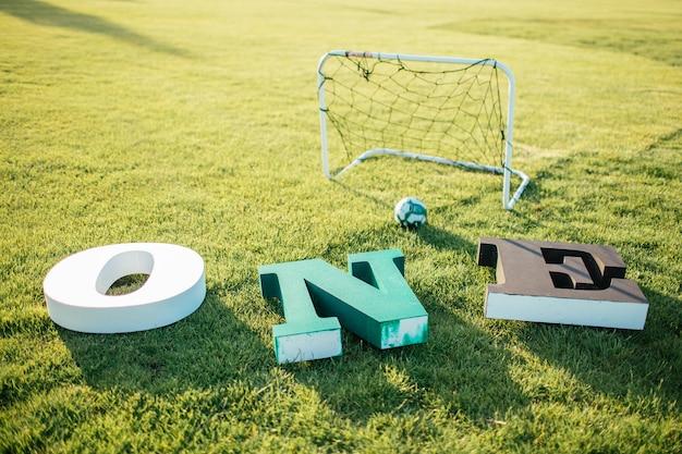 サッカーゴール近くの緑の草の上に横たわる白、緑、黒の文字の1つ。写真1年の赤ちゃんのための装飾
