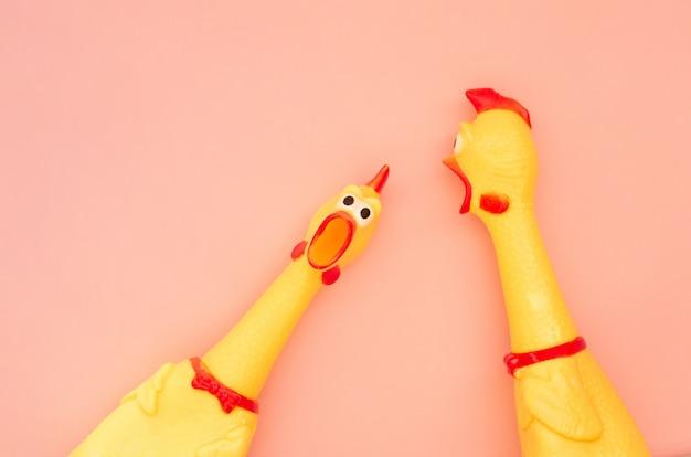びっくりした鶏のおもちゃはパステルピンクの背景に分離されています。1つはカメラを見て叫び、もう1つは横を向きます。サンゴの背景に鶏のおもちゃを叫んでください。