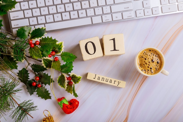 コンピューターのキーボードと飾られたクリスマスツリートップビューコピースペースとコーヒーカップとオフィスデスクテーブル1月1日元旦