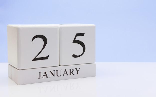 1月25日月の25日目、反射と白いテーブルに毎日のカレンダー