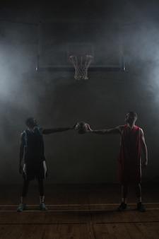 1つのバスケットボールを保持している2つのバスケットボール選手