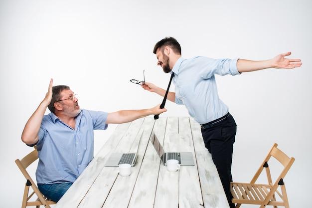 ビジネス紛争。 1人の男性が相手のネクタイをつかんでいる間に2人の男性が否定性を表明