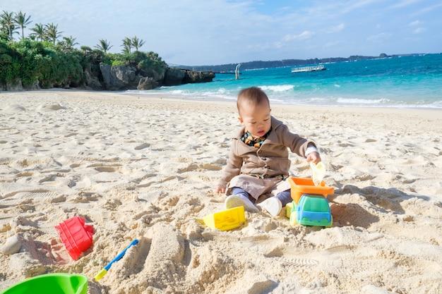 かわいい小さなアジア1〜2歳の幼児の赤ちゃん男の子子供座って&美しい砂浜の熱帯のビーチでおもちゃを遊んで
