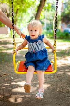 Портрет ребенка 1-2 лет. счастливая кавказская девушка ребенка играя игрушки на спортивной площадке. девушка улыбается. дети и спортивная концепция.