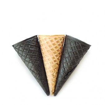 1つのベージュと2つの黒い空のアイスクリームコーン。白い背景に分離します。