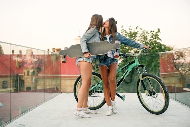 特別装備の展望台で魅力的なショートパンツで彼女の熱い女性の友人を待っている自転車を持つ1つのトレンディな30代の女の子