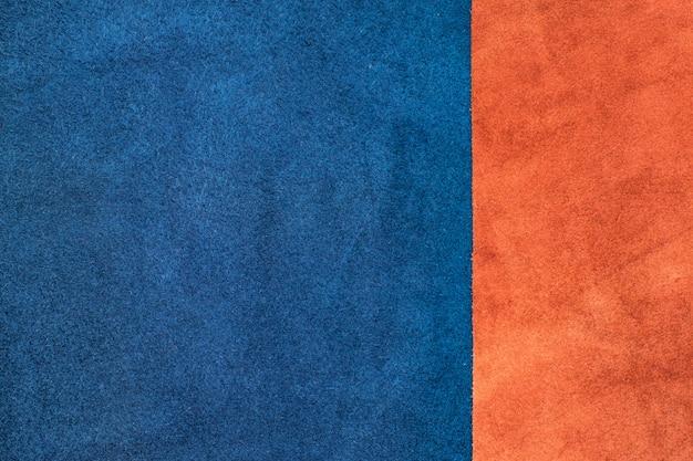 スエードのネイビーブルーとオレンジの革を1/3の比率のテクスチャのバックグラウンドで仕切ります