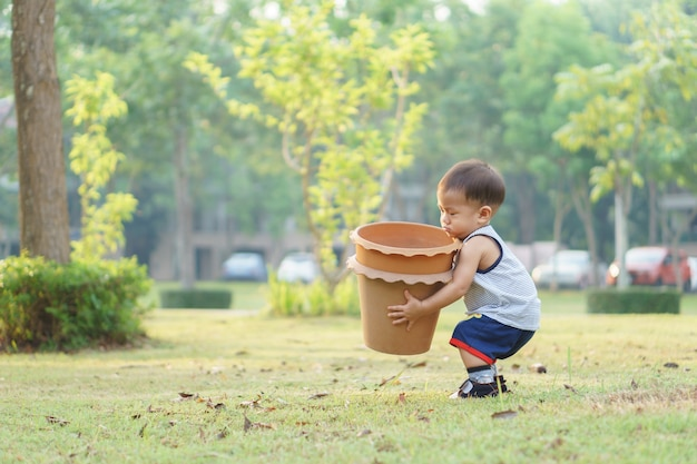 1年4ヶ月アジアの赤ちゃんは、いくつかの木を植えようとする