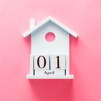 木製カレンダー1 4月のばかの日。ピンクの背景にフラットを置きます。