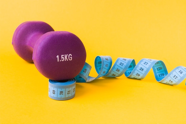 黄色の表面に1.5キログラムの紫色のダンベルと青い巻尺