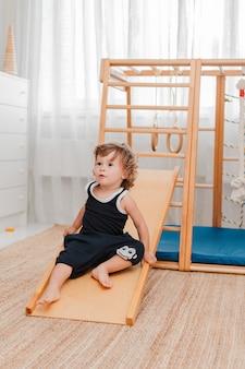 幼い1.5歳の子供は、家庭の子供の木製スポーツ施設に従事しています。
