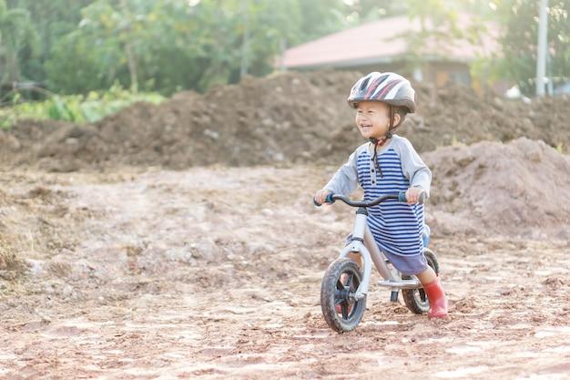 約1年9ヶ月のアジアの男の子が泥の建設道路にベビーバランスバイクを乗っています