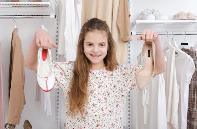 1 10 세 백인 십대 소녀가 밝은 베이지 톤의 옷을 입은 옷장 표면에 신발을 손에 쥐고 있습니다.