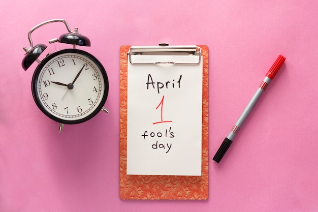 1 april fool's day, notebook, clock, pen. flat lay on pink background.