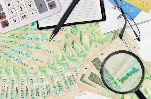 1 бразильские реальные купюры и калькулятор с очками и ручкой.