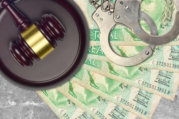 1 бразильский реальный банкнот и молоток судьи с полицейскими наручниками на столе суда. понятие судебного разбирательства или взяточничества. уклонение от уплаты налогов или уклонение от уплаты налогов